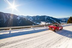 Vintage racing car driving classic rally on snow covert road. Red vintage racing car driving a classic rally on snow covert road on mountain Planai  in Austria Royalty Free Stock Photos