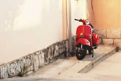Red vintage scooter parked near a building wall Royalty Free Stock Images
