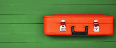 Red vintage suitcases with black handle on the wooden green background. Retro travel luggage. Space for  design. Top view. Concept: tourism, travel and Stock Photo