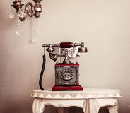Red Vintage Telephone. Old red vintage / retro telephone in the room with white walls Stock Photo