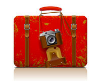Red vintage threadbare suitcase with a retro photo camera Stock Photos