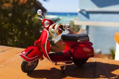 Red vintage toy scooter or motorbike with golden and silver wedding rings on it in the background of sea view Stock Photos