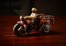 Red vintage toy tricycle on dark wooden table.  Stock Photos