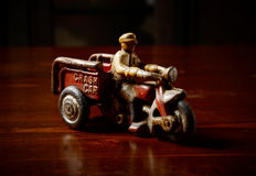 Red vintage toy tricycle on dark wooden table. Background Stock Image