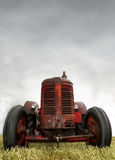 Red Vintage Tractor. An old red rugged vintage tractor with real patina Stock Photography