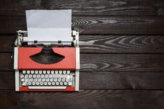 Red vintage typewriter with white blank paper sheet on dark wooden table royalty free stock photo