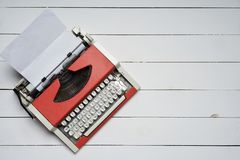 Red vintage typewriter with white blank paper sheet on white wooden table royalty free stock images