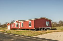Red Vinyl Siding on New Manufactured Home. New manufactured home with red vinyl siding and windows with white lineals royalty free stock photography