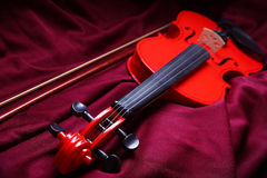 Red Violin. A violin lies on red fabric stock images
