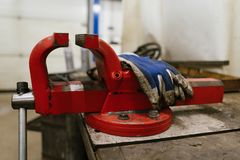 Red vise, taken from the side, with dirty blue protective gloves over it, in a garage of a car repair shop. Red vise, taken from the right side, with dirty blue stock images