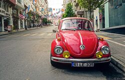 Red Volkswagen Beetle Parked at Road Side Near Pedestrian Lane Royalty Free Stock Photography