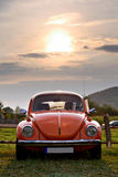 Red Volkswagen Beetle. With sun above it at sunset Royalty Free Stock Photography