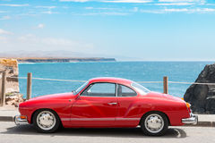 Red Volkswagen. Old red car parked on a side of a road with blue ocean and sky in the background stock photo
