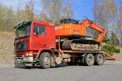Red Volvo F12 Intercooler Hauls a Hitachi Zaxis Excavator Royalty Free Stock Images