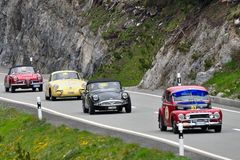 A red Volvo PV544, a dark green Daimler SP250, a yellow Porsche 356 and a red Alfa Romeo Giulia spider. ZERNEZ, SWITZERLAND - JUNE 15: A red Volvo PV544, a dark Stock Photography