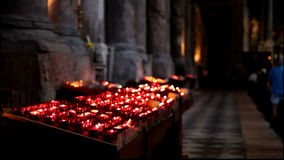 Red votive candles burn inside a church during mass stock video
