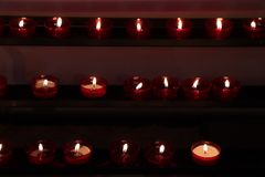 Votive candles in a church. Red Votive candles, burning in a dutch protestant Christian church royalty free stock image
