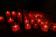 Red Votive Candles in a Church. Group of warm glowing candles on black background with copy space stock photo