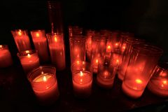 Red Votive Candles in a Church. Group of warm glowing candles on black background with copy space royalty free stock images