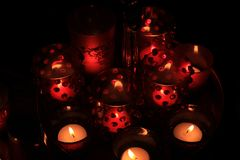 Red votives and candles. Red candles and votive lights burning in a christmas arrangement royalty free stock photography