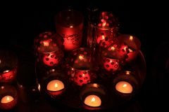 Red votives and candles. Red candles and votive lights burning in a christmas arrangement stock images