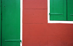 Red vs. Green: Door and Window in Detail. Red wall of a house with green door and window shutters in New Orleans, Louisiana, USA Stock Image