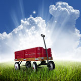 Red wagon. A red magic wagon (radio flyer) with wooden rails and stars and light shining from the bed. Concept for the magic a child gives to their toys stock photo