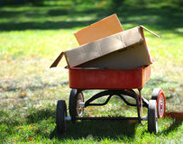 Red Wagon With Cardboard Boxes in Park Setting Royalty Free Stock Images