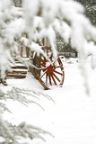 Red wagon wheel. An old red wooden wagon wheel in a snow covered woods Royalty Free Stock Photos