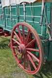 Red Wagon Wheel. A red wagon wheel attached to a green wagon Stock Image