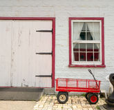 Red wagon, white walls and red trim background. Royalty Free Stock Image