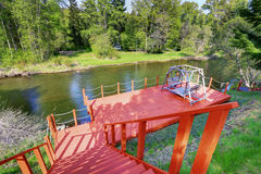 Red walkout deck with staircase on river bank. Backyard view. Stock Photography