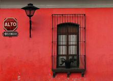 Red wall. A red wall with a stop sign, a window and a lantern,  located in Antigua Guatemala Royalty Free Stock Photos