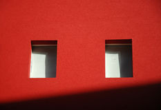 Red wall. Bright red wall with two windows and diagonal shadow Stock Photography