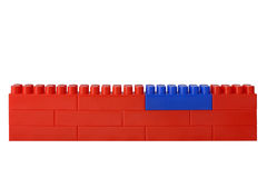 Red wall from blocks of the children's designer. One block on green is replaced royalty free stock images