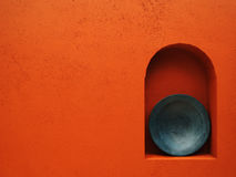 Red wall with blue plate Royalty Free Stock Photos