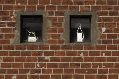 Red Wall Ceramics. Two unfinished ceramic pots in the windows of a red brick wall Royalty Free Stock Photo