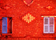 Red wall and colored shutters. Bright red brick wall with two colored shuttered windows stock image