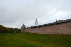 Red wall of the Kremlin with a corner tower next to a moat cover royalty free stock images