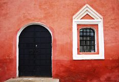 Red wall in Kremlin, Rostov Velikiy, Russia. The window with reflection and the black metal door Royalty Free Stock Photo