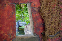 Red wall with netting and open window. With vies of a pond royalty free stock photos