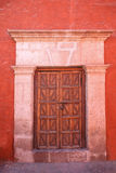 Red wall with old decorative stonedoor. Royalty Free Stock Image