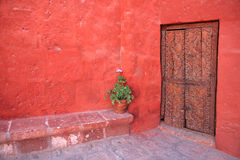 Red wall with old decorative wood door. Stock Photo
