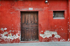 Red Wall and Old Door. In Antigua, Guatemala Royalty Free Stock Photo