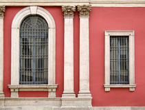 Red wall and ornate windows. Two different windows on a red wall. One small, one big. Additional columns and decorative elements Stock Photo