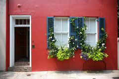 Red wall with white and black shutters Stock Photography