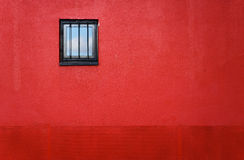 Red wall with window. Red painted wall with small barred window, sky reflected within Royalty Free Stock Photo