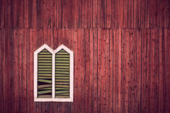 Red wall with window frame. Red wooden rustic wall with window and broken shutters Stock Photo