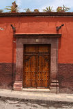 Red wall with wooden doors and cactus on the roof Royalty Free Stock Image