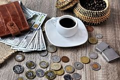 Red wallet with american dollars, various foreign coins and cup of coffee on the table royalty free stock photo